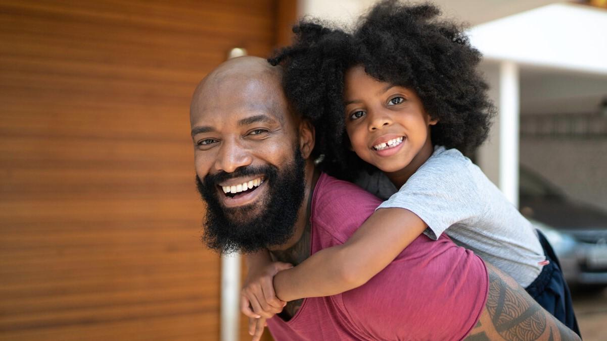 Homem negro segurando sua filha nas costas, os dois estão sorrindo