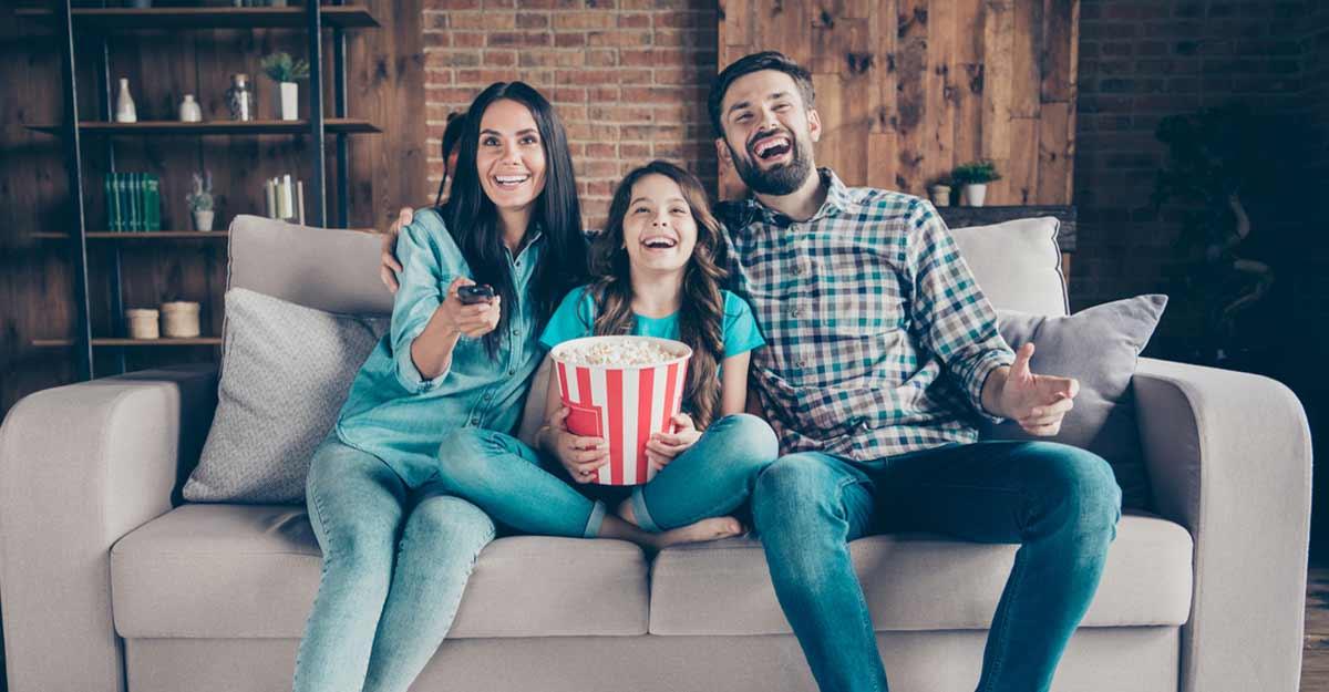 Família reunida no sofá assistindo a filmes com mensagens importantes