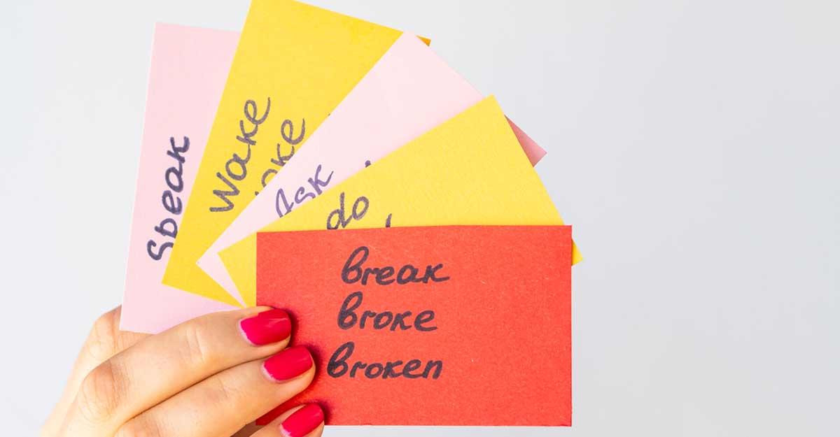 Mão feminina segurando alguns cartões escritos alguns modal verbs