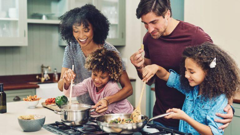 Pai e mãe cozinhando com suas filhas