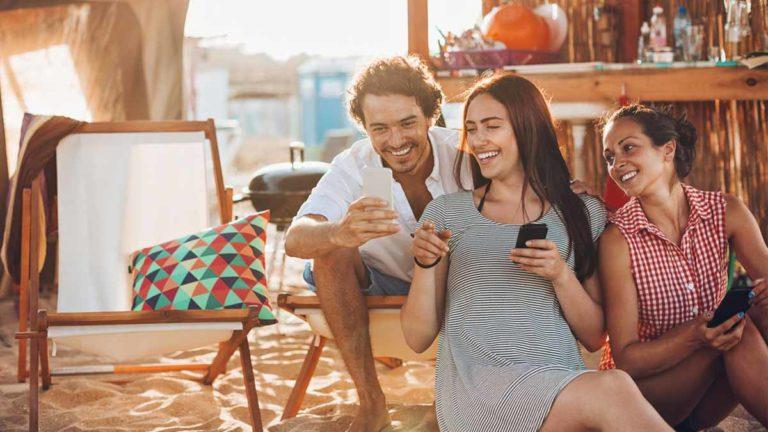 Três amigos, um homem e duas mulheres, sentados na areia olhando a tela do celular na mão do homem