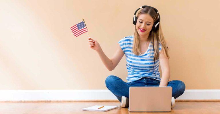 Menina sentada no chão e olhando o computador com uma pequena bandeira na mão