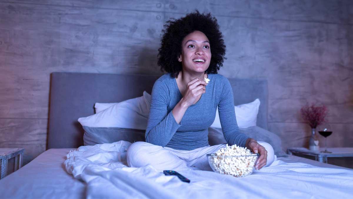 Mulher em sua cama assistindo filmes que lembram a infância