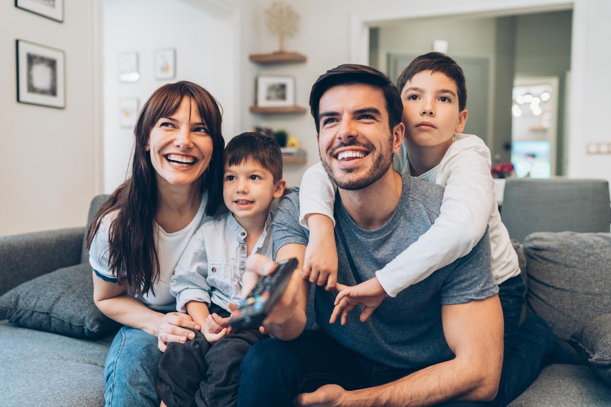 Família sentada no sofá assitindo TV