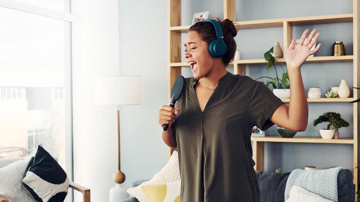 Garota com fone de ouvido e escova na mão simbolizando um microfone, ela canta músicas de desenhos em inglês