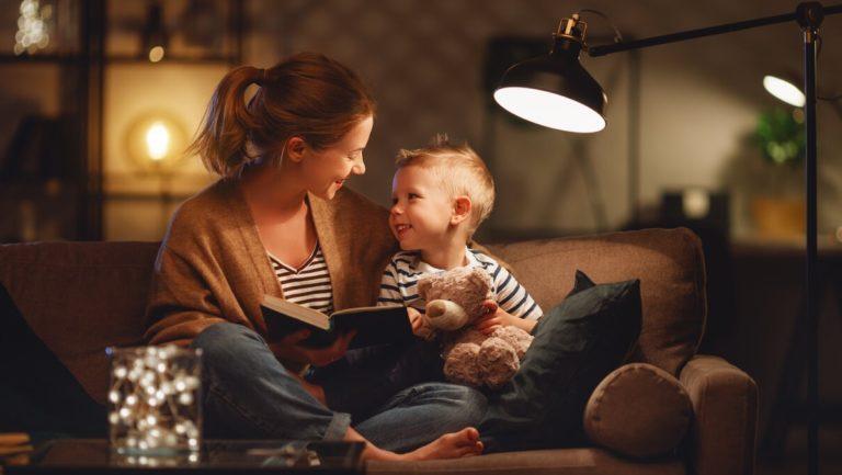 Uma mulher sentada no sofá com seu filho pequeno no colo, ela lê um livro pra ele