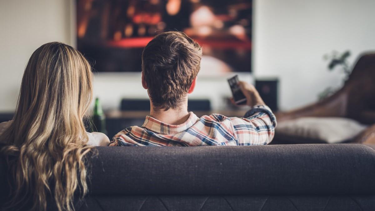 Casal sentado no sofá assistindo um filme na TV