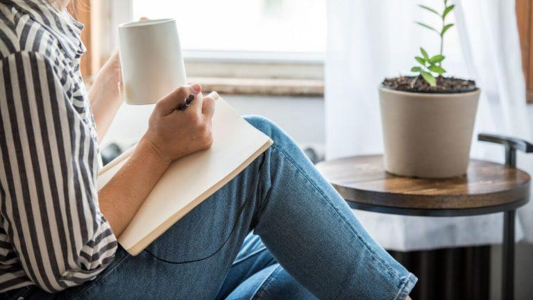 Caderno apoiado na perna de uma mulher que faz anotações nele enquanto estuda o present perfect
