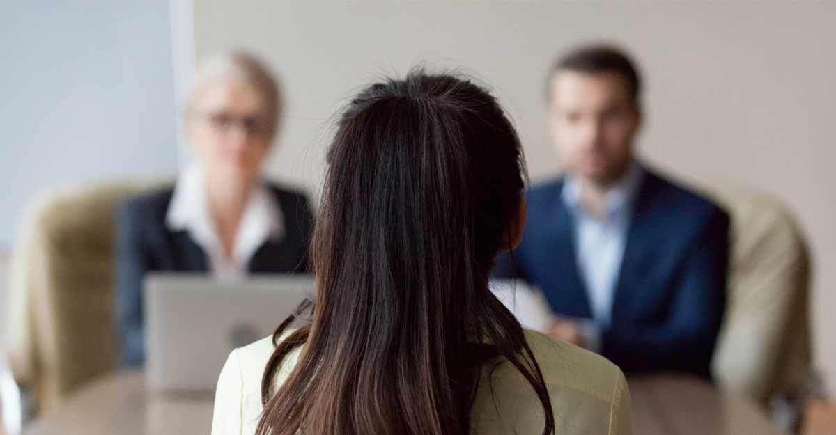 Mulher jovem fazendo uma entrevista de emprego em inglês com dois entrevistadores