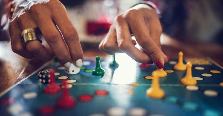 Mãos jogando em um tabuleiro
