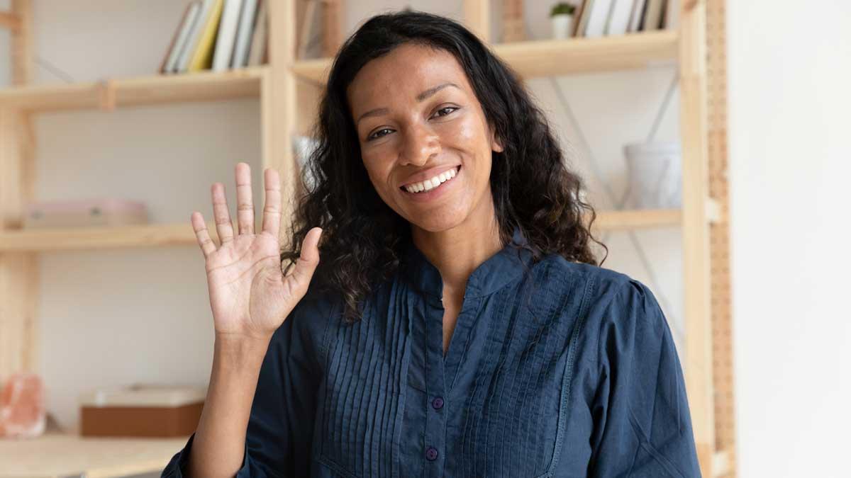 Mulher cumprimentando com um aceno de mão