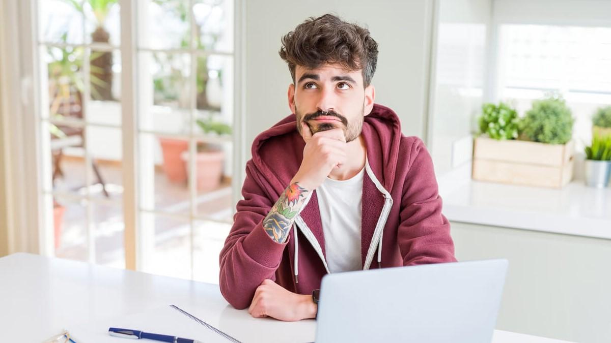 Jovem com computador e livros na mesa, com a mão no rosto e com uma expressão de dúvida