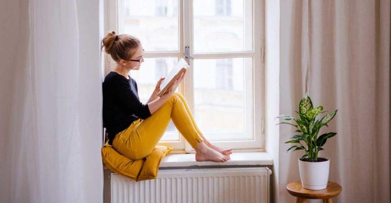 Mulher sentada na janela lendo um livro em inglês