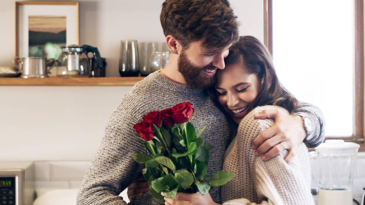 mulher-segurando-buque-de-flores-abraçada -com-namorado