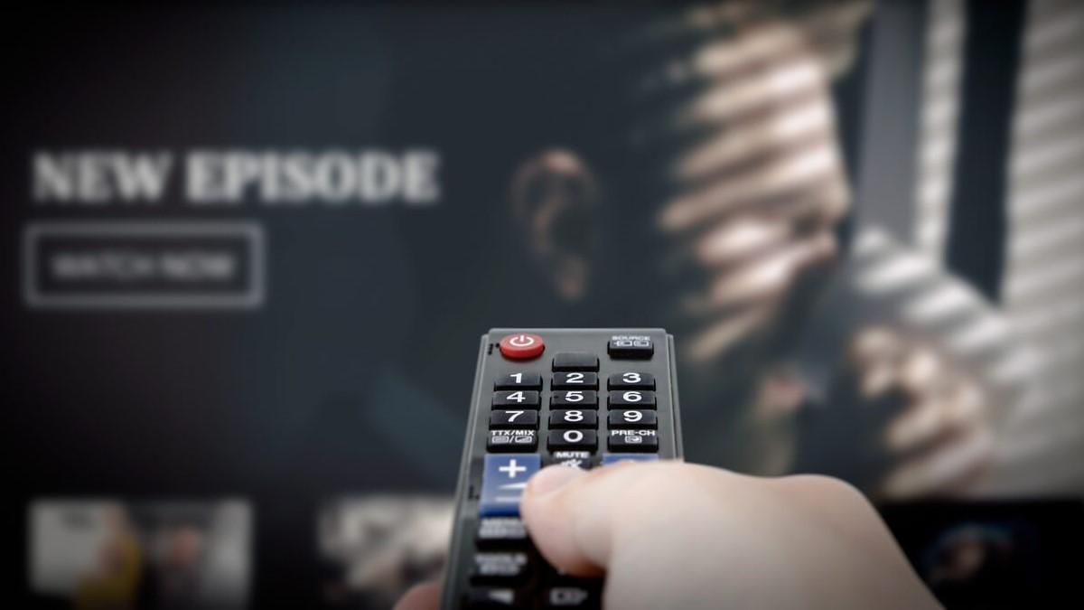 Uma mão segurando um controle remoto e ao fundo uma televisão com a imagem de uma série