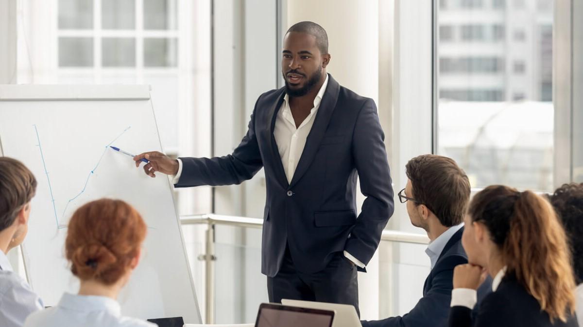 Homem negro fazendo uma apresentação de trabalho para alguns colegas de equipe