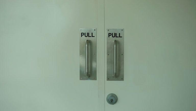 """duas portas brancas e duas maçanetas, uma diz """"pull"""" e outra """"push"""""""