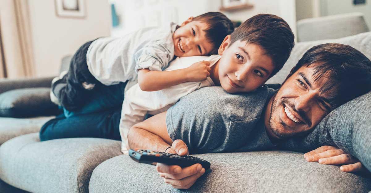 Pai deitado com seus dois filhos no sofá vendo filme