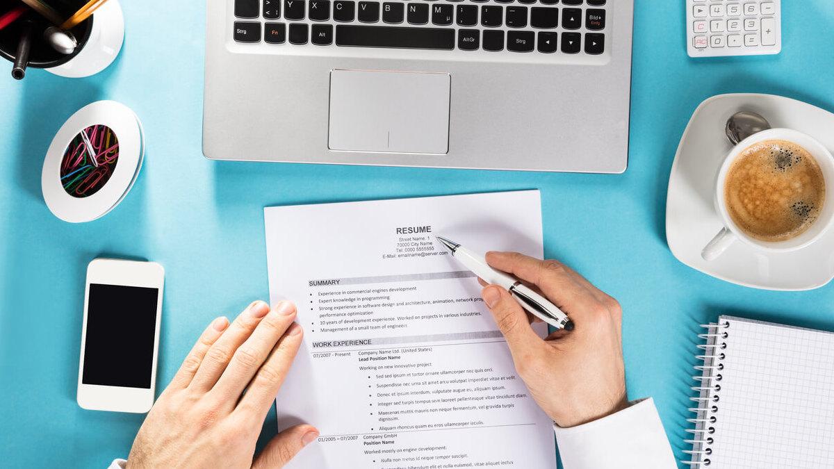 homem revisando currículo na frente do notebook
