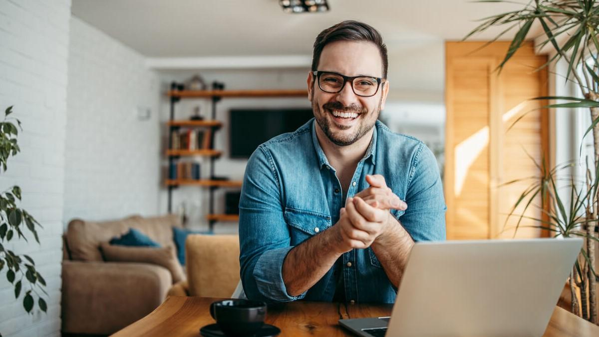 Homem jovem sentado em uma mesa com computador e sua sala de casa ao fundo