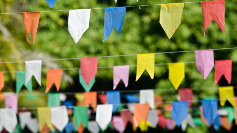 Diversos cordões pendurados com bandeirinhas típicas de festa junina