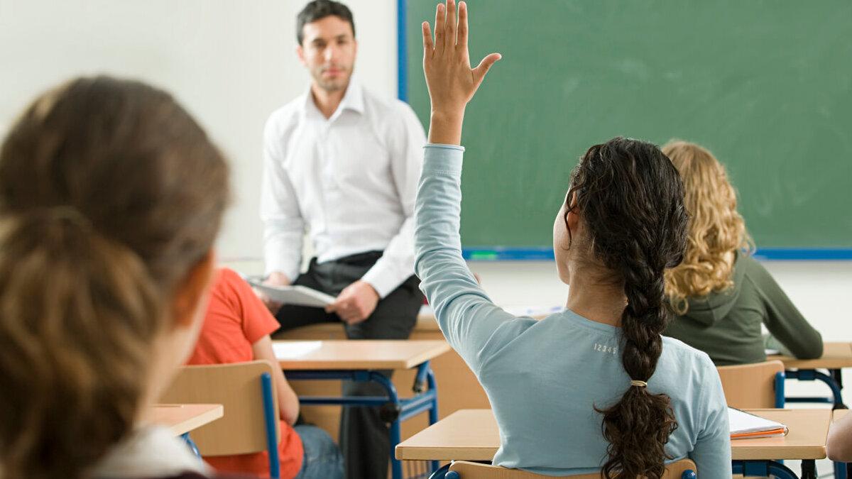 Aluna com a mão levantada em sala de aula