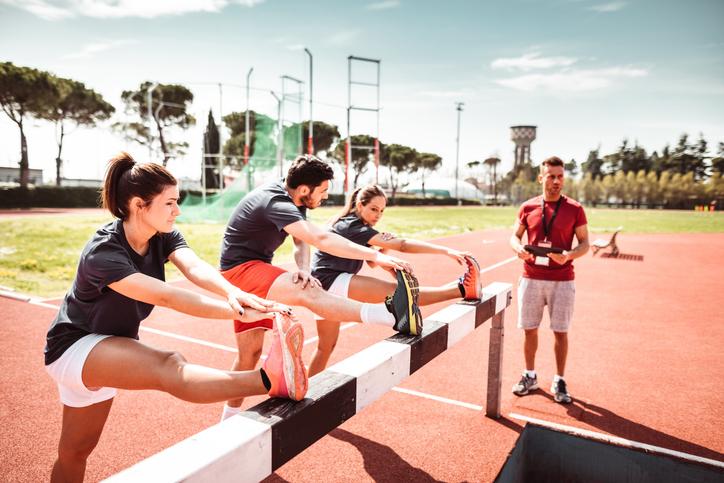 Atletas se alongando em pista de atletismo