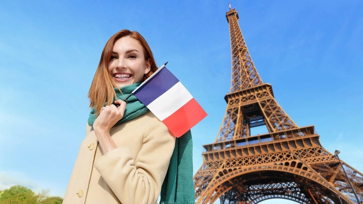 Moça em frente a Torre Eiffel segurando a bandeira da França