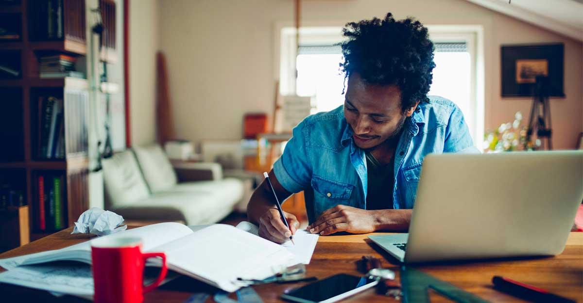 Jovem em uma mesa de estudos com computador e livros sobre phrasal verbs