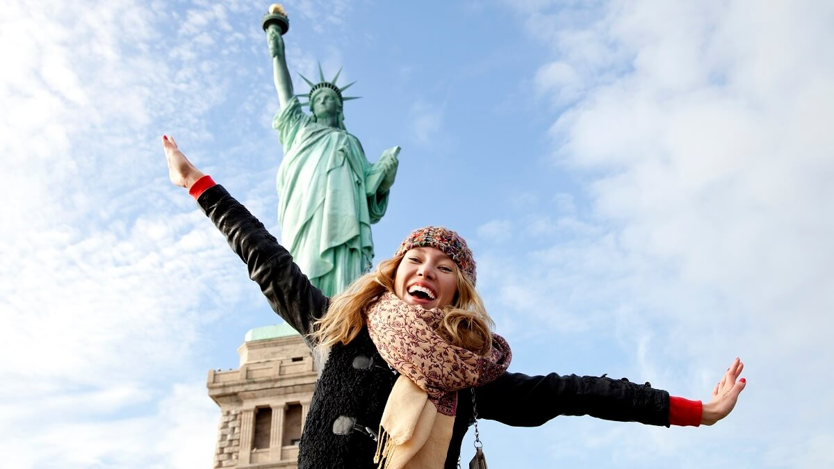 Adolescente em frente a Estátua da Liberdade nos Estados Unidos