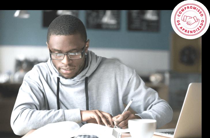 Homem negro sentado estudando sobre livro e selo no canto superior direito de Compromisso de Aprendizado Wizard Idiomas