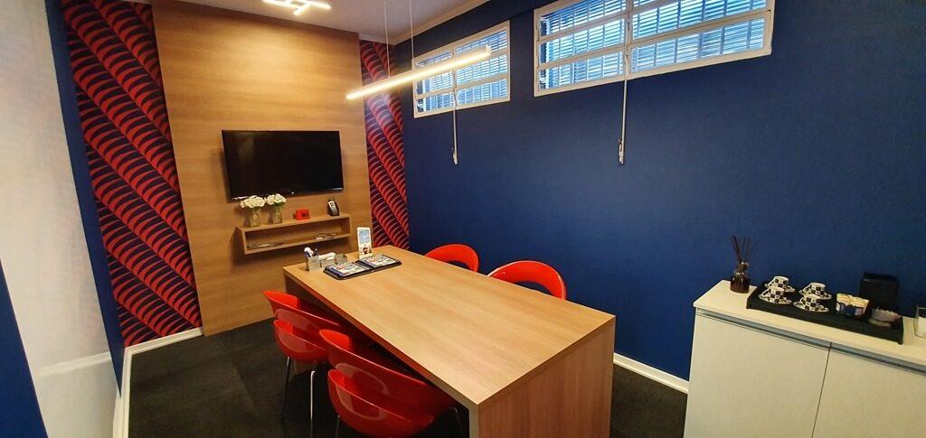 Sala com mesa, cadeiras e televisão na escola de idiomas Wizard by Pearson