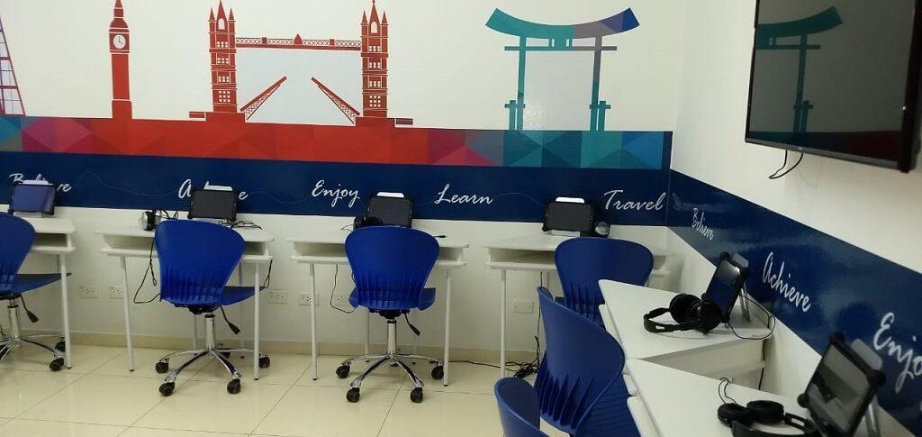 Sala de aula com bancada, cadeiras e tablets na escola de idiomas Wizard by Pearson
