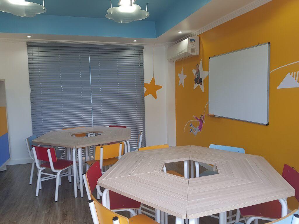 Sala de aula de inglês para crianças com mesas e cadeiras escola Wizkids