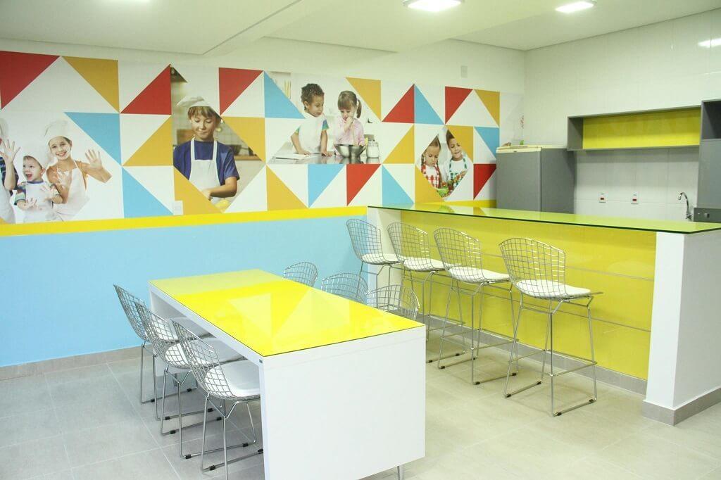 Cozinha para aula especial de culinária para crianças com mesas, cadeiras, pia, geladeira na escola Wizkids