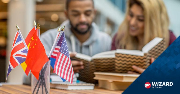 Algumas mini bandeiras de vários países na mesa e casal branco lendo livros