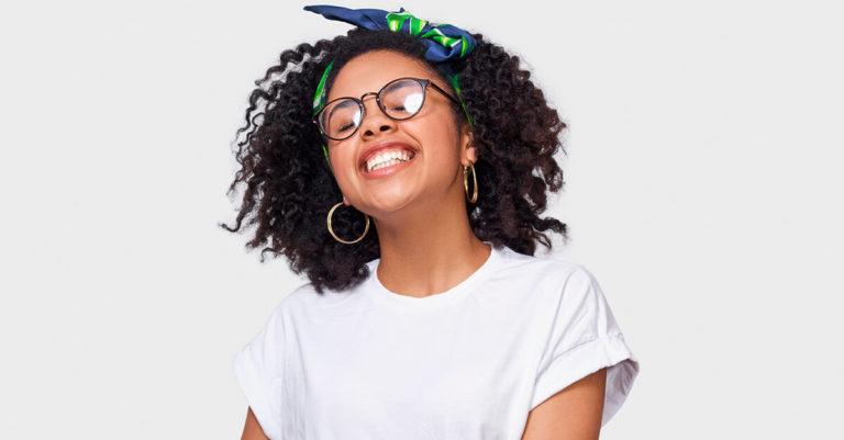 menina de camisa branca, laço na cabeça e óculos sorrindo