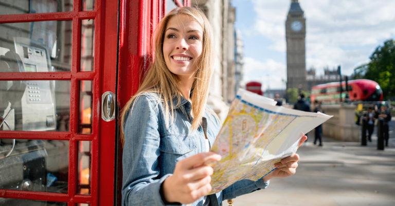 mulher loira com mapa na mão decidindo qual passeio fará em Londres