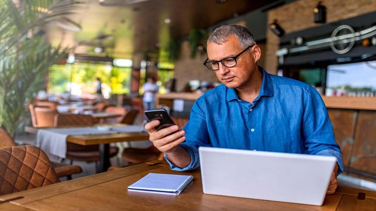 homem de camisa jeans e óculos com computador e celular na mão