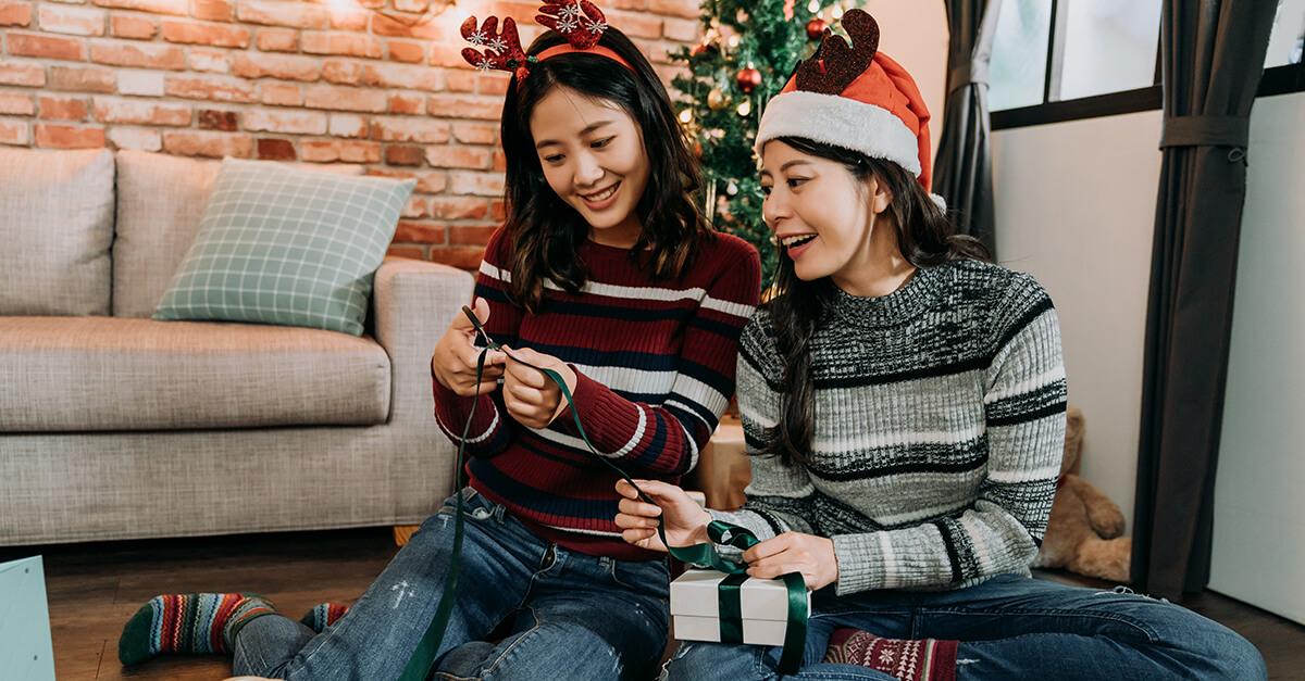 duas meninas sentadas no chão da sala com adereços de natal na cabeça