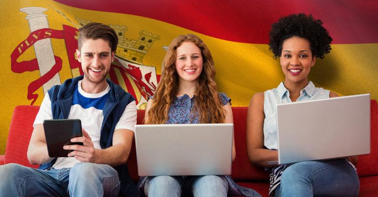 2 mulheres e 1 homem sentados com computador nas mãos em frente uma parede com a bandeira da espanha