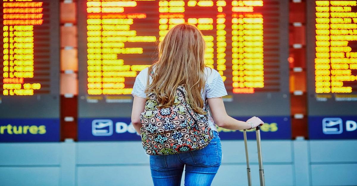mulher com mala e mochila olhando o painel do aeroporto