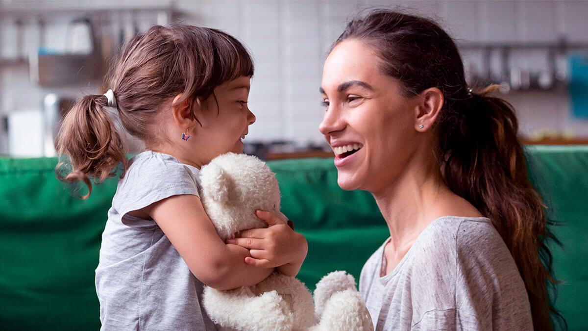 mulher conversando com uma criança que está segurando um urso de pelúcia
