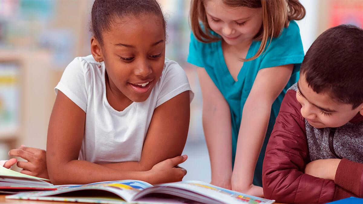 3 meninas lendo um livro e estudando inglês