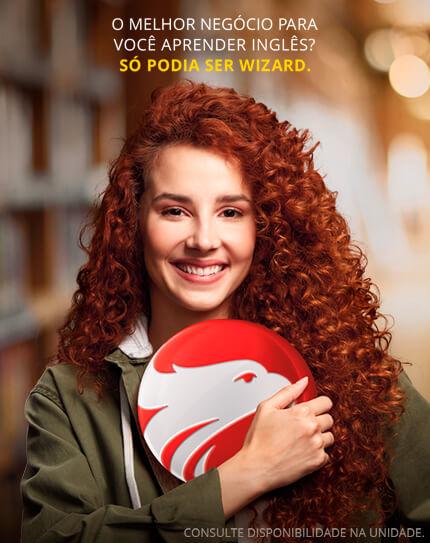 Mulher branca ruiva sorrindo segurando o logo da Wizard com a frase