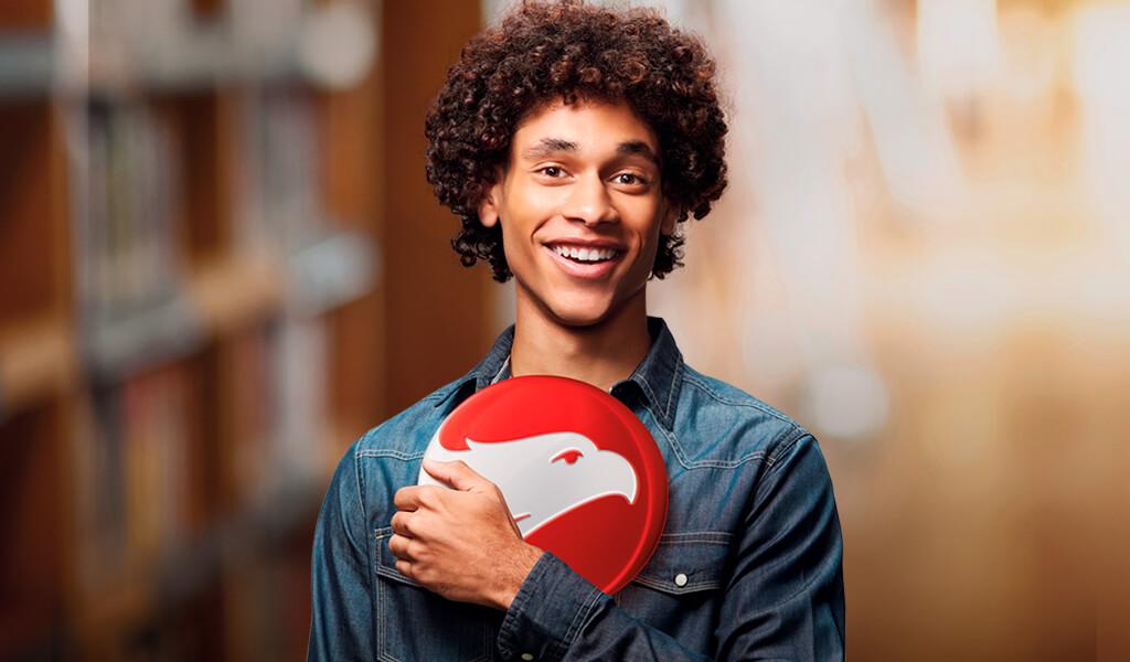 Rapaz negro sorrindo e segurando o logo da Wizard