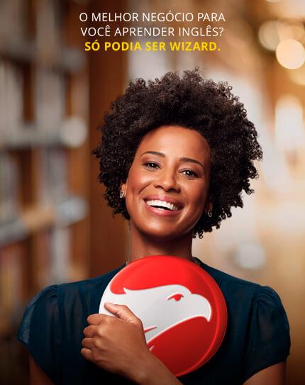 Mulher negra de blusa azul marinho sorrindo segurando o logo da Wizard com a frase O melhor negócio para você aprender inglês? Só podia ser Wizard no topo.