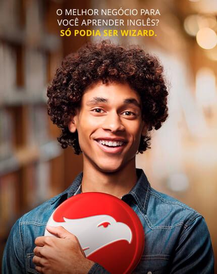 Rapaz negro sorrindo e segurando o logo da Wizard com a frase