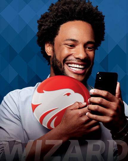 Homem negro sorrindo segurando um celular com a mão esquerda e com a direita segurando o logo da Wizard com a escrita Wizard na parte inferior