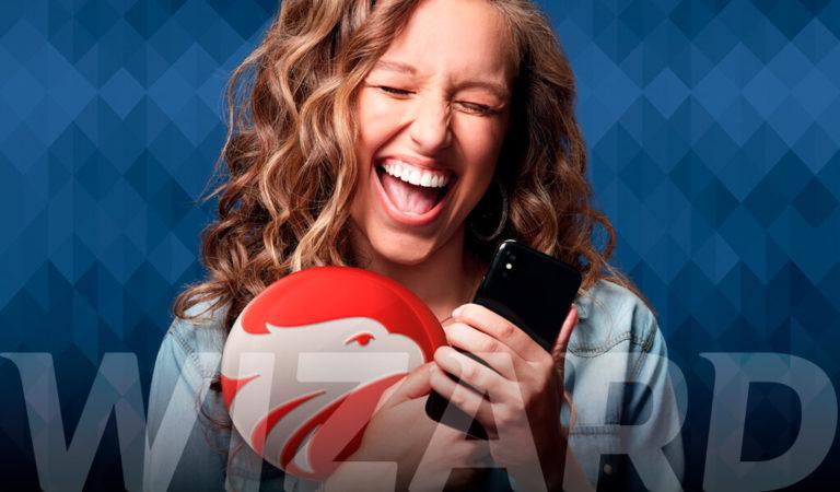 Mulher loira sorrindo de olhos fechados segurando um celular com a mão esquerda e com a direita segurando o logo da Wizard com a escrita Wizard na parte inferior